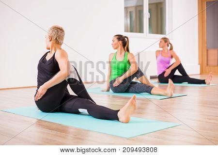 Three girls practicing yoga, Matsyendrasana / Spine-Twisting Pose