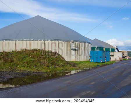 Biogas energy plant on farm in countryside with blue sky, Schleswig-Holstein, Germany.