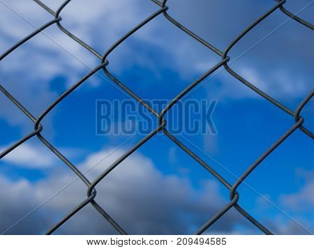 Closeup of metal fence with square units in front of dramatic blue cloudy sky.
