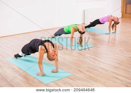 Three girls practicing yoga, Setuasana / Bridge pose