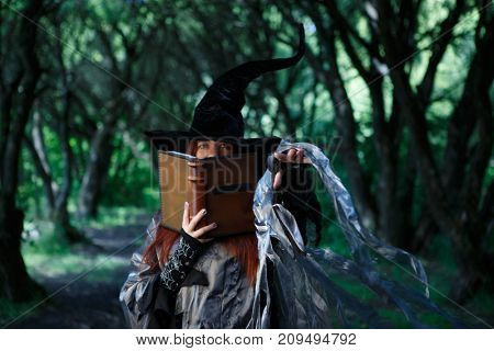 Image of witch with magic book of spells and outstretched hand against dark forest
