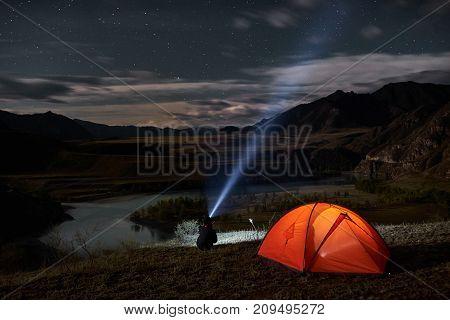 Man tourist with flashlight near his camp tent at night. Orange illuminated tent.
