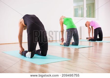 Three girls practicing yoga, Ushtrasana / Camel pose