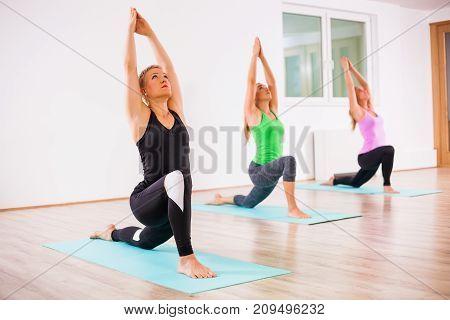 Three girls practicing yoga, Virabhadrasana / Warrior 1 pose
