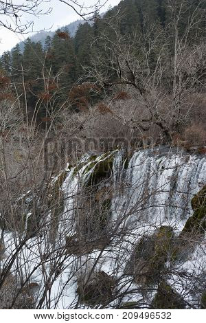 Waterfall in the forest. Frozen water drains over the rocks. The rock is covered with moss on which cold water flows.Branches of a tree above a waterfall