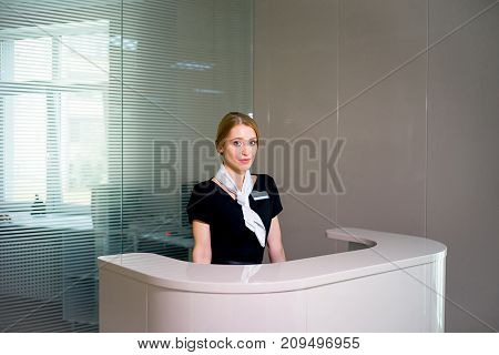 Friendly concierge at office reception behind the counter