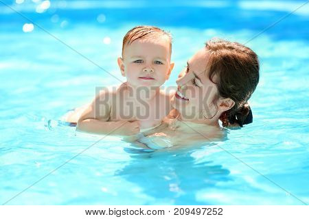 Child swimming lesson. Cute little boy learning to swim with mother in pool