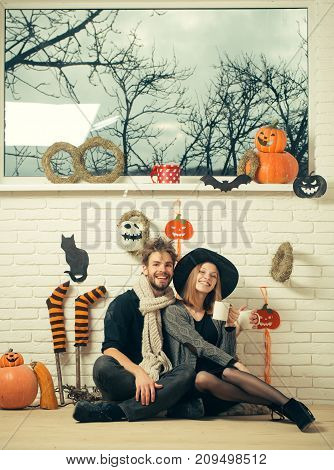 Halloween autumn holiday celebration concept. Macho smiling in scarf. Couple in love with cups sitting under window. Happy woman in witch hat. Festive and homely atmosphere.