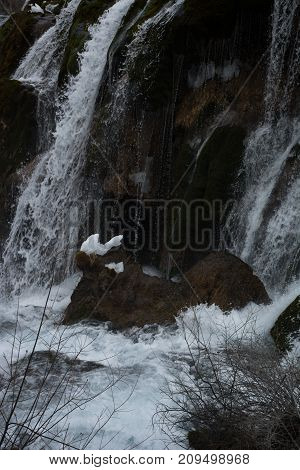 Waterfall in the forest. Frozen water drains over the rocks. The rock is covered with moss on which cold water flows.Water flow to rocks