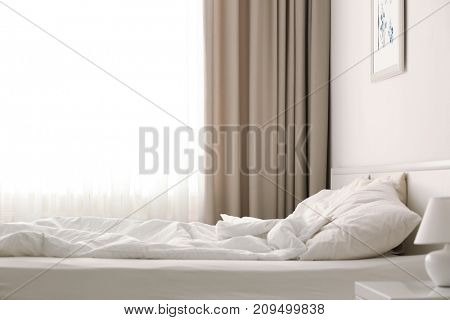 Cozy bed near window with beautiful curtains in room