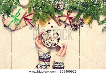 Female hands in a New Year's sweater with a cup of hot cocoa with marshmallows Christmas gift Spruce branches Cones Orange slices Snowflakes. Traditional festive decoration light background top view. Vintage Style with Drawn Snowfall