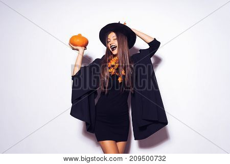 happy girl in a Halloween costume and a witch's hat is holding a pumpkin