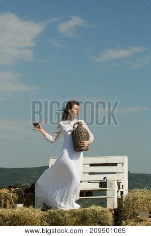Winery tour concept. Summer vacation holidays and celebration. Woman with glass of red wine and wicker bottle. Girl in white dress posing on blue sky. Model with alcohol drink on sunny day.