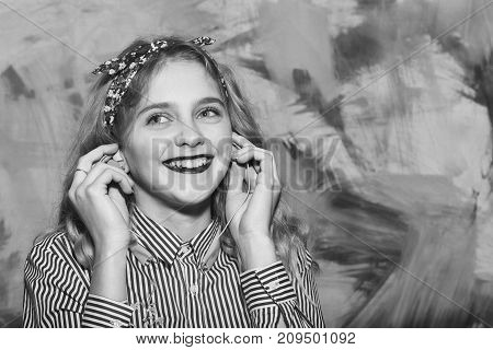 Cheerful pretty girl or beautiful woman with red lips and blond hair in blue striped shirt and stylish headband listens to music with earphones indoors on colorful wall on abstract background
