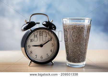 Glass of water with chia seeds and alarm clock on table