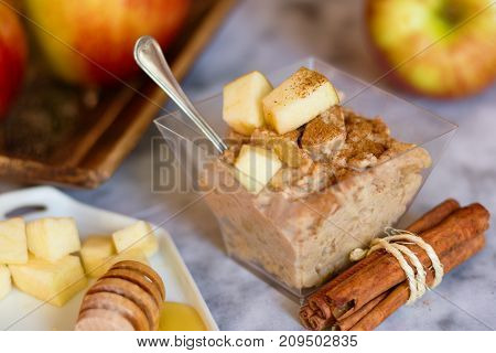 Square shaped glass bowl of oatmeal porridge with apples cinnamon and honey on marble surface