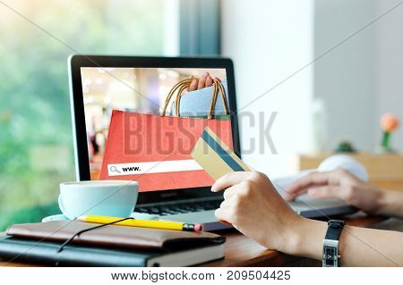Woman hand holding credit card and using laptop computer with www. on search bar over blur store screen background shopping on line business and technology concept digital marketing