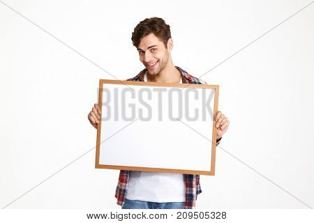 Portrait of a happy young guy holding blank board and looking at camera isolated over white background