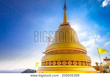 Big golden Stupa of a Buddhist temple against blue sky, Thailand. Tourist attraction