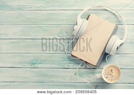 Audio book concept. Headphones, coffee and old book over wooden table. Top view with space for your text. Toned
