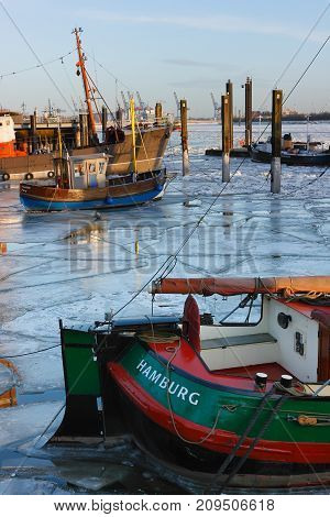 Hamburg, Germany - February 15, 2012: Vintage fishing boat in the icy captivity at the pier in Hamburg. Elbe river in winter.