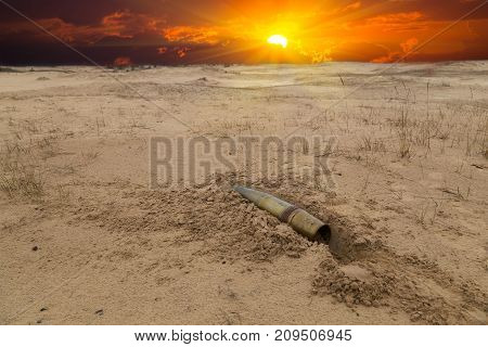 old artillery metal projectile on the sand in the desert against the background of a blood-red dramatic sunset. concept of war