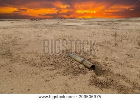 old artillery metal projectile on the sand in the desert against the background of dramatic sunset. concept of war