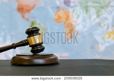 Judge's gavel and over world map. Symbol for jurisdiction. Law concept a wooden judges gavel on table in a courtroom or law enforcement office on blue background. Copy space for text