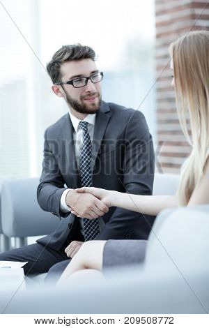 close-up of a manager shakes hands with a regular customer.