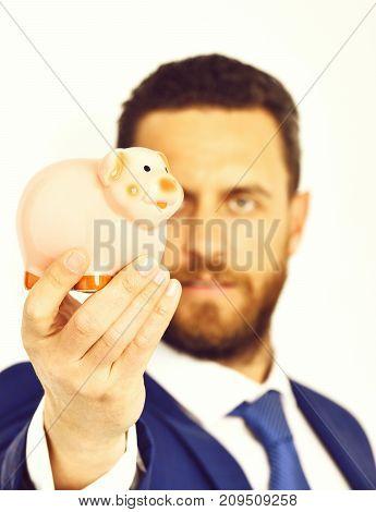 Piggybank In Hand Of Businessman In Suit And Tie