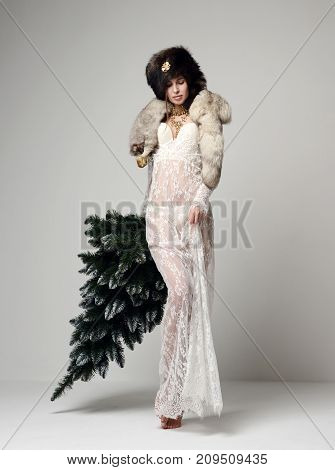 Young glamour russian woman with winter christmas tree decoration in fur hat skin vulpes lagopus new year background