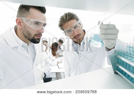 closeup. scientist and assistant studying the solution in the glass tube