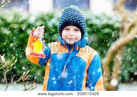 Little kid boy feeding birds in winter. Cute happy preschool child hanging colorful selfmade bird house on tree on frosty cold day. Preschooler in colorful wam clothes. Nature, empathy with animals.