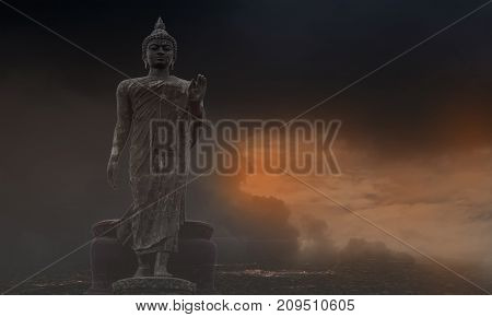 The Buddha stood in a black clouded day covered with light orange.