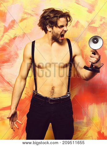 Caucasian Bearded Macho Man In Pants With Suspenders Holding Lamp
