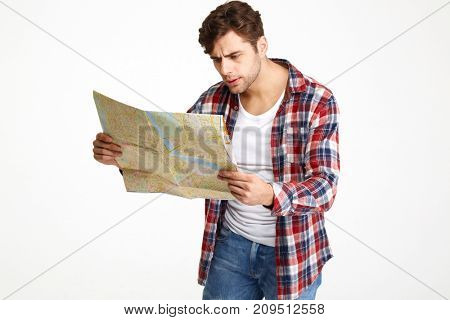 Portrait of a puzzled young man looking at travel map isolated over white background