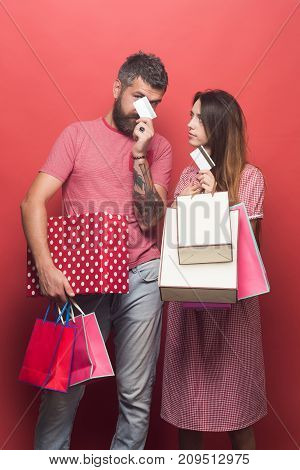 Couple Holds Shopping Bags And Credit Cards On Coral Background