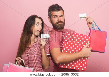 Couple in love holding big box and packets showing credit cards on pink background. Guy with curious face and pretty lady do shopping. Man with beard near young lady. Shopping and spending concept