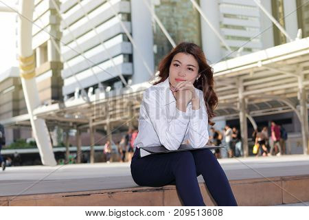 Portrait of leader young Asian business woman thinking and sitting on stairway in urban building background.