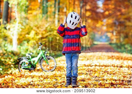 Little kid boy in colorful warm clothes in autumn forest park with a bicycle. Active child putting safe helmet before cycling on sunny fall day in nature. Safety, sports, leisure with kids concept.