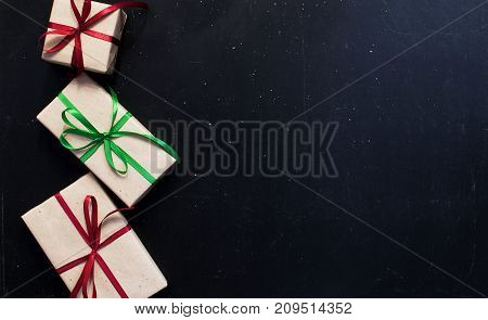 Traditional Christmas dark background top view. New Year's gifts with red and green ribbon.