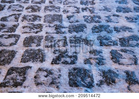 Photo of pavers strewn snow. Winter night.