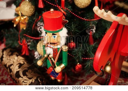 a toy nutcracker under a New Year's fur-tree
