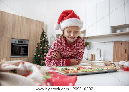 Portrait of hungry little girl looking at sweet pastry on tray with appetite. She is wearing Santa Claus red hat and smiling while standing in kitchen