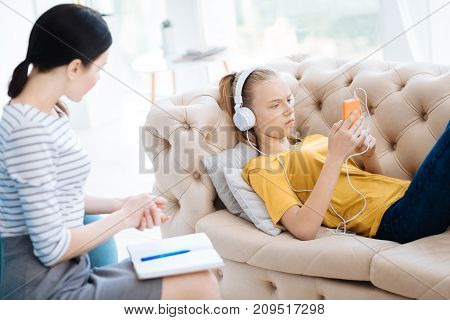 Relaxing music. Unhappy depressed young woman wearing headphones and listening to music while trying to relax
