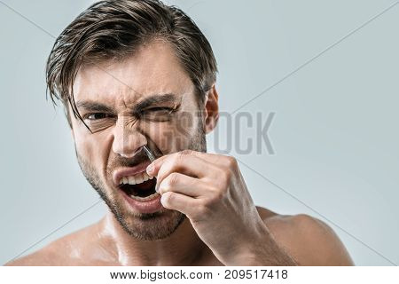 Man Plucking Hair From Nose