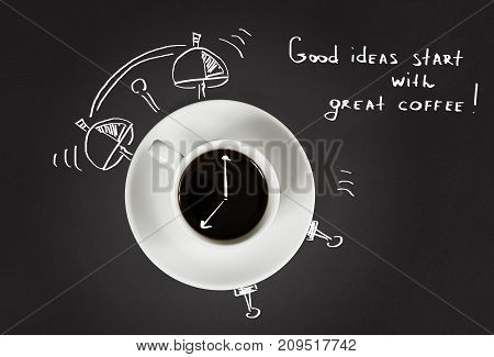 Good morning coffee and alarm clock concept on black slate background, top view