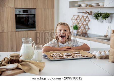 Portrait of excited little female child baking holiday cookies with enjoyment. She is standing near tray and smiling