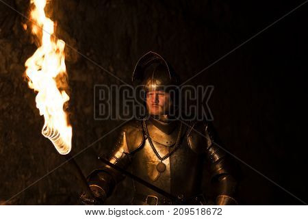 Knight With A Torch And Sword At Night On A Wall Background