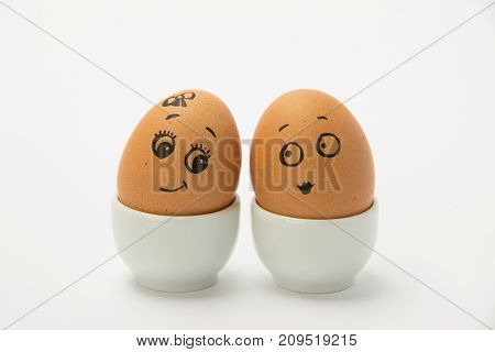 Two chicken brown eggs with the faces of a boy and a girl in love on a white background